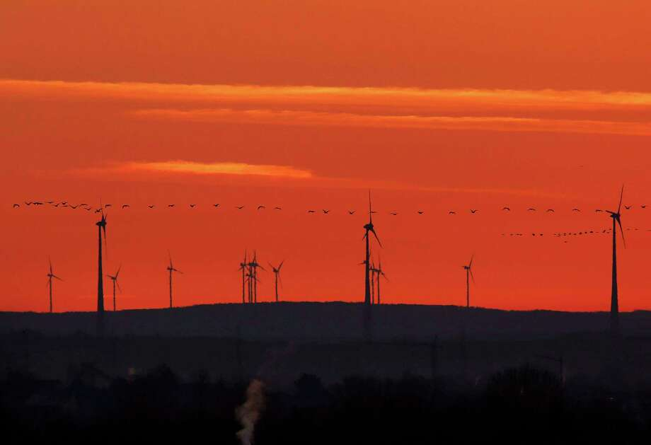"""FILE - In this March 28, 2017 file photo a swarm of birds flies past wind turbines just before sunrise in the outskirts of Frankfurt, Germany. A senior EU official says Wednesday, May 31, 2017, the EU and China will reaffirm their commitment to the Paris climate change accord this week, regardless of whether President Donald Trump pulls out of the pact. The official told reporters that the EU and China will also """"spell out"""" how they plan to meet their commitments to the accord at talks in Brussels on Friday. (AP Photo/Michael Probst,file) Photo: Michael Probst, STF / Copyright 2017 The Associated Press. All rights reserved."""