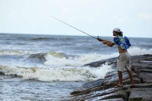 Evan Gideon fishes in Galveston amid some choppy waves Tuesday. Galveston officials say residents should prepare for heavy rain, strong wind and possible tidal flooding.