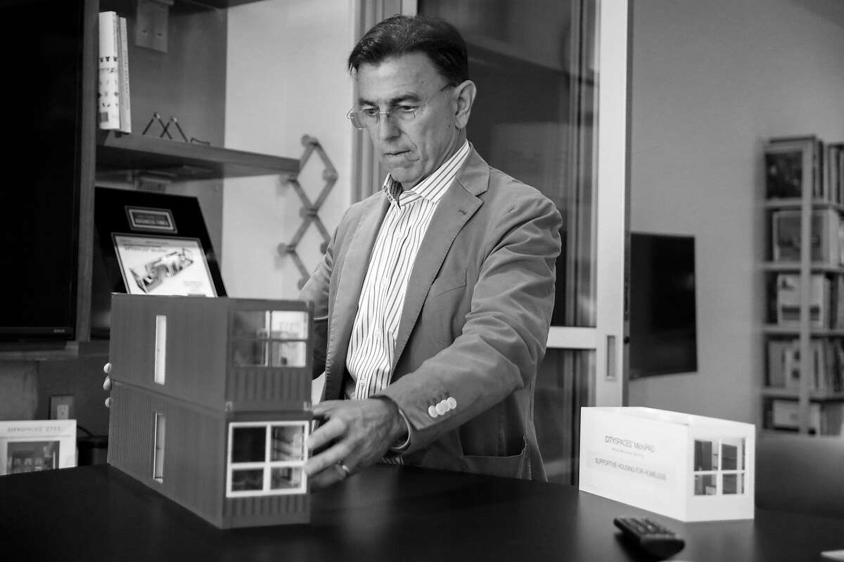 """Patrick Kennedy, a developer who will build small, stackable housing units for free then rent them to the city as alternative housing for the homeless, shows off a model """"micro pad"""" in his office in San Francisco."""