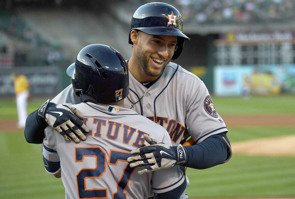 OAKLAND, CA - JUNE 20: George Springer #4 of the Houston Astros is congratulated by Jose Altuve #27 after Springer hit a lead off home run against the Oakland Athletics in the top of the first inning at Oakland Alameda Coliseum on June 20, 2017 in Oakland, California.