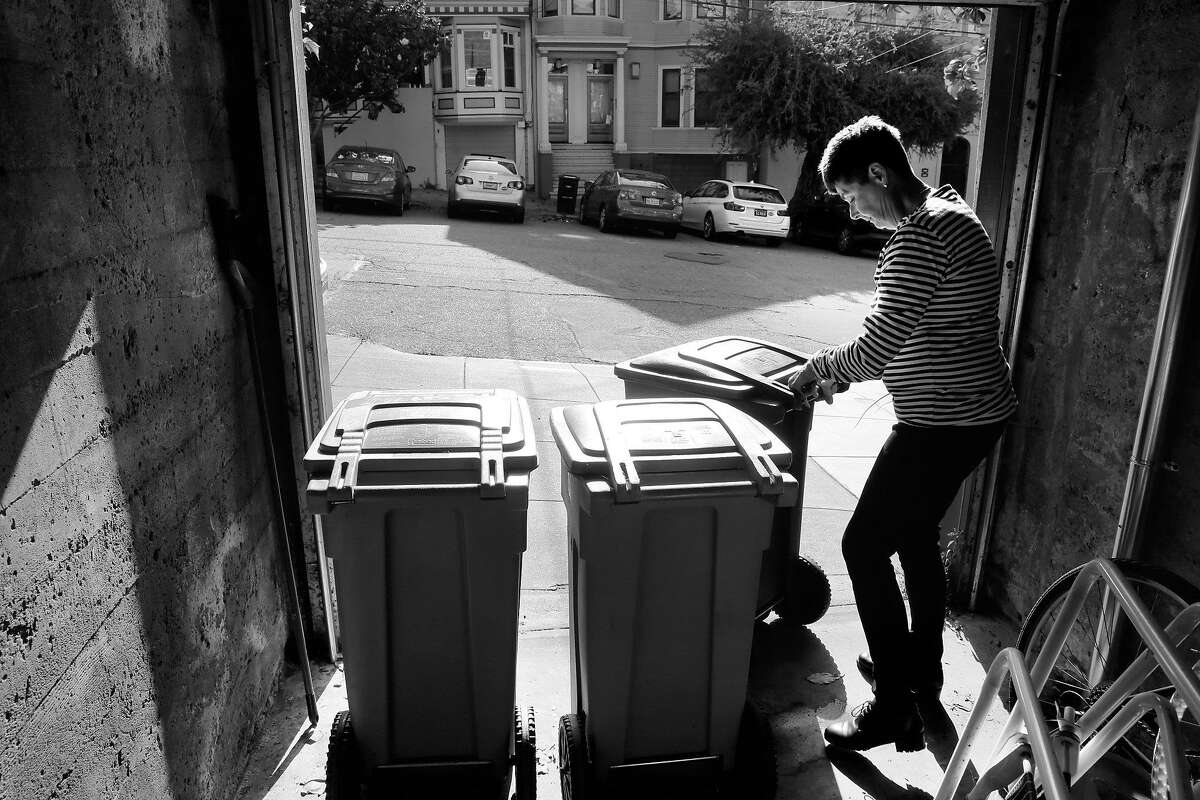 Marcy Fraser puts out her garbage can for pick up, on Tuesday June 6, 2017, in San Francisco, Ca., but waiting till early morning to put out the recycling can due to the homeless who camp nearby and rummage through her cans at night looking for recyclables creating a mess on the street and sidewalk.