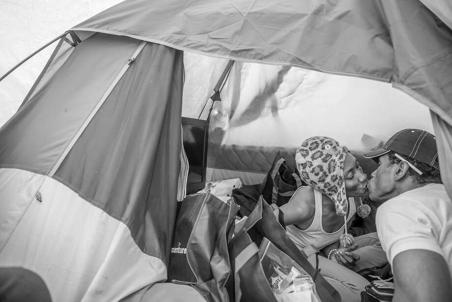 China Richardson (left) and her longtime partner, Khadaffii King, kiss in their tent before King heads out for a smoke break near 5th and Market streets in Oakland. Photo: Santiago Mejia, The Chronicle