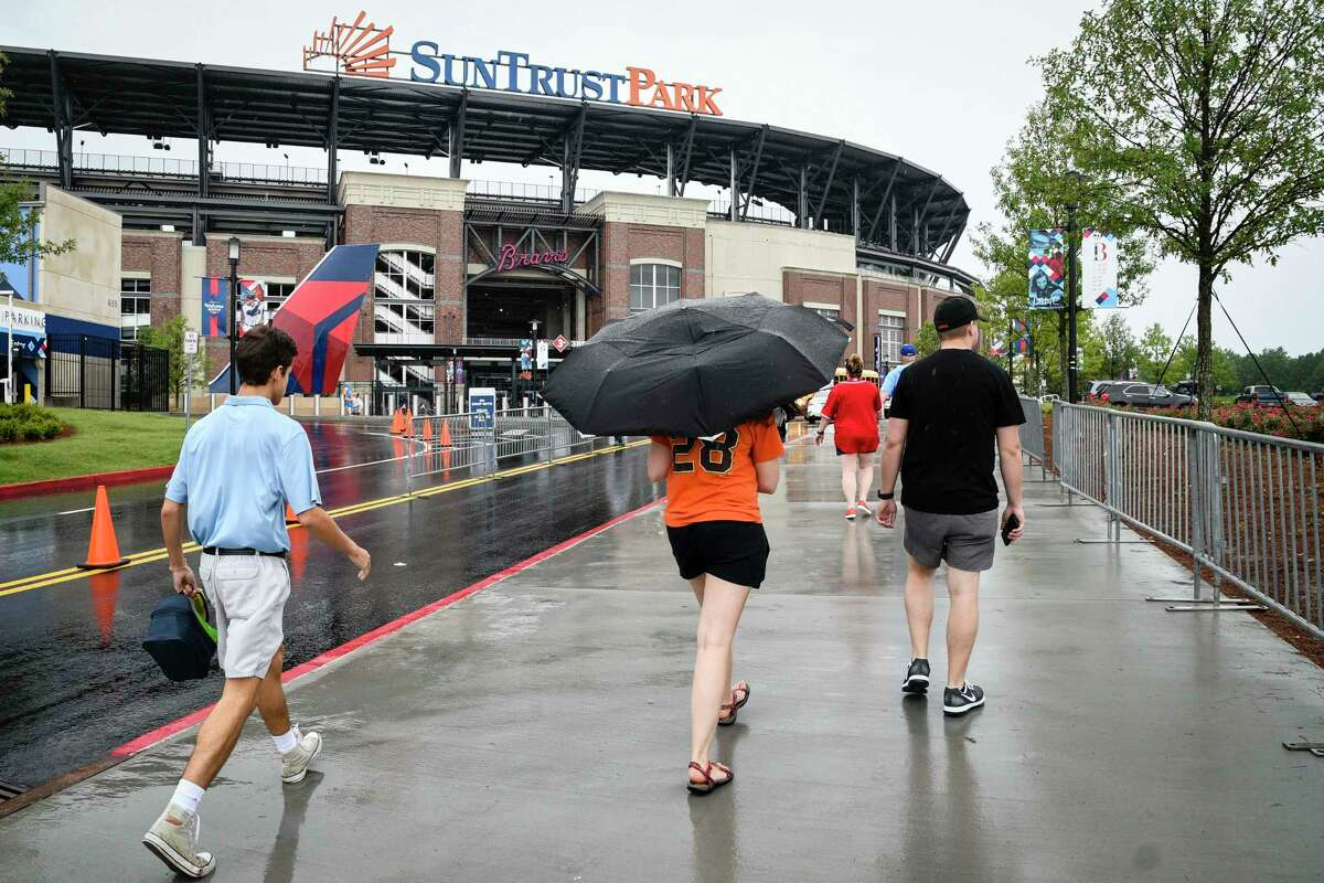 Fans arrive at SunTrust Park for the Atlanta Braves' baseball game against the San Francisco Giants, Tuesday, June 20, 2017, in Atlanta. Tropical Storm Cindy has been causing rain in much of the Southeast.