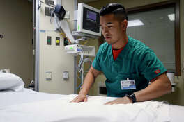 Thomas Pham, a registered nurse at Christus St. Elizabeth Hospital, prepares a bed for a patient during his shift in the intensive care unit on Tuesday. Photo taken Tuesday 6/13/17 Ryan Pelham/The Enterprise