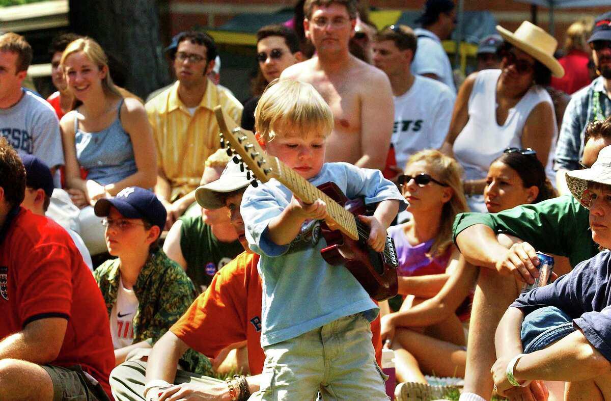 Times Union staff photo by MICHAEL P. Farrell --Two-year-old Simone Gillogy of Portland , Maine pretends to play along with the Jazz/Funk group Soul Live during the 2002 Freihofer's Jazz Festival at SPAC in Saratoga Springs , New York Saturday, June 29, 2002.