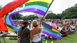 "Rocio Castillo, right, and her friend ""Carol,"" stand under a rainbow flag in Hermann Square as they celebrate the 2016 Houston Pride Festival, Saturday, June 25, 2016, in Houston. ""It's very special because Orlando touched my heart,"" Castillo said.  ( Jon Shapley / Houston Chronicle )"