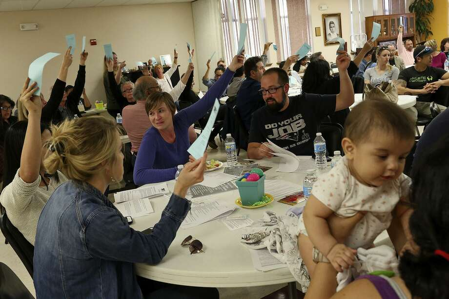 Residents including Lauren and Chris Mongeon, center, vote for amending bylaws during a Dignowity Hill Neighborhood Association meeting at the Ella Austin Center on March 21, 2016. At right is Xochitl Guerra, five months, held by her mother, Marjorie Moh-Guerra, who came to the meeting with her husband and their son to find out more about the neighborhood they want to move into. Photo: Lisa Krantz / Lisa Krantz / SAN ANTONIO EXPRESS-NEWS