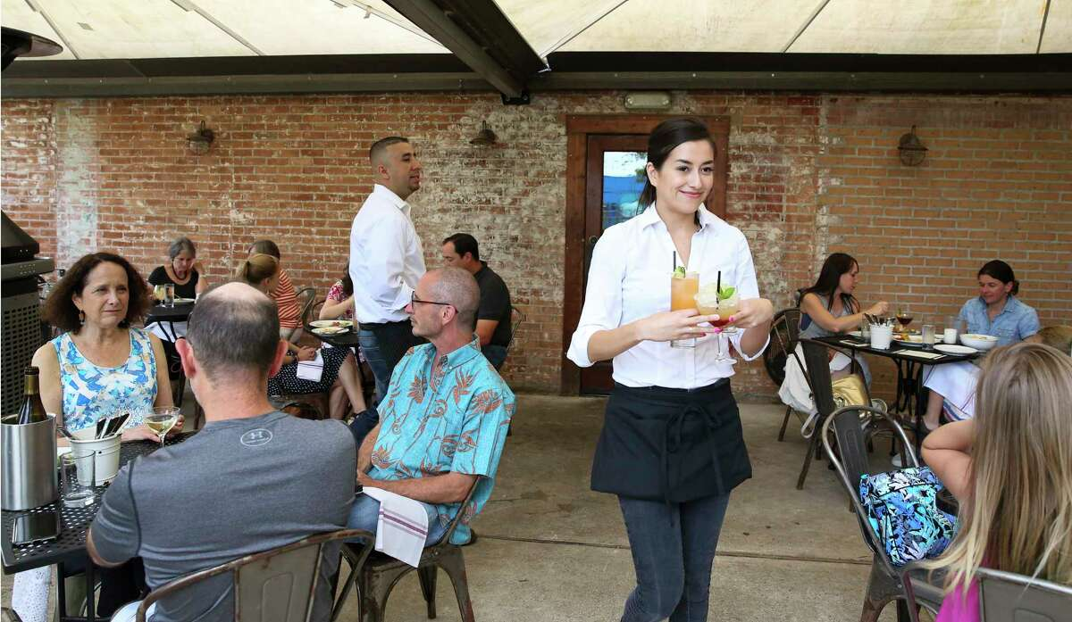 Coltivare cocktail waitress Jacqueline Valle delivers drinks to guests at the restaurant's garden Friday, June 9, 2017, in Houston. Parts of the Heights that still have alcohol sales restrictions are starting a petition to allow establishments to sell mixed drinks.