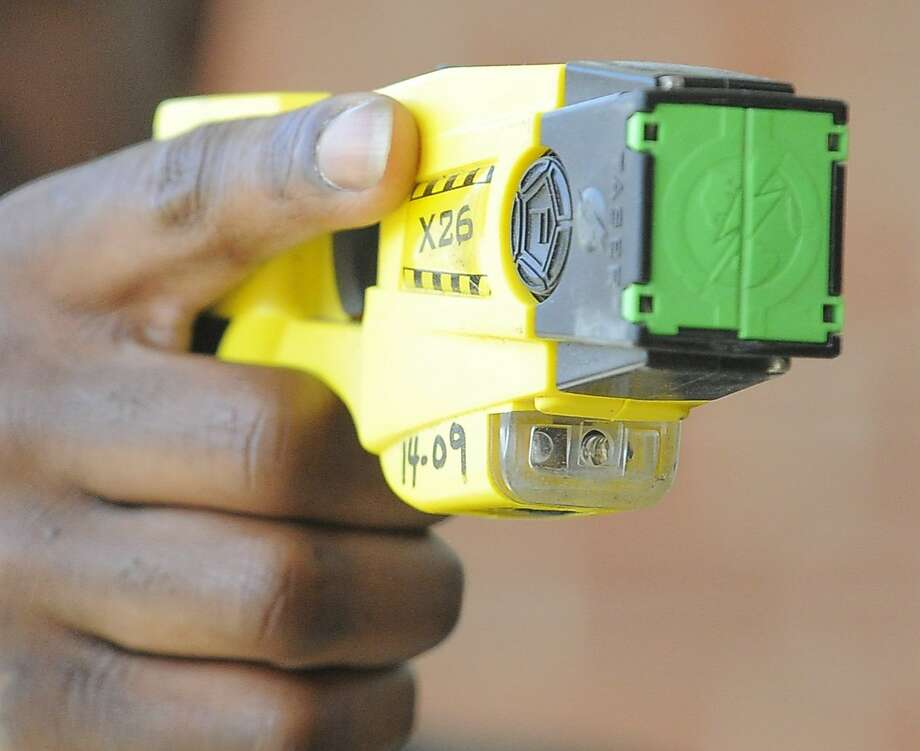 A Stamford Police Officer holds a Taser X26 Stun Gun on April 1, 2016. Blacks and Hispanics are shot with stun guns more often in Connecticut, while whites are given the benefit of a warning far more often, a Hearst review of state data from 2015 shows. Stamford police, however, only shot three people with a stun gun last year. Photo: Matthew Brown, Hearst Connecticut Media