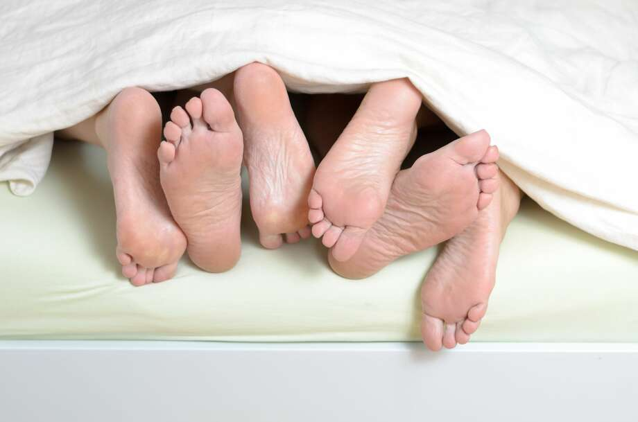 Three pairs of feet in bed, mixed all over Photo: Michael Heim / EyeEm/Getty Images/EyeEm