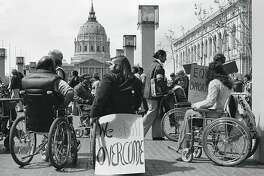 Section 504 protestersdemonstrate with signs andplacards outside SanFrancisco�s City Hall, April 5,1977.