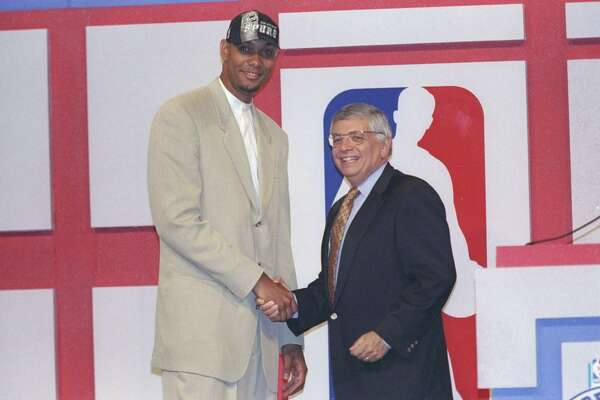 Center Tim Duncan of the San Antonio Spurs shakes hands with NBA commissioner David Stern during the 1997 draft at the Charlotte Coliseum on June 25.
