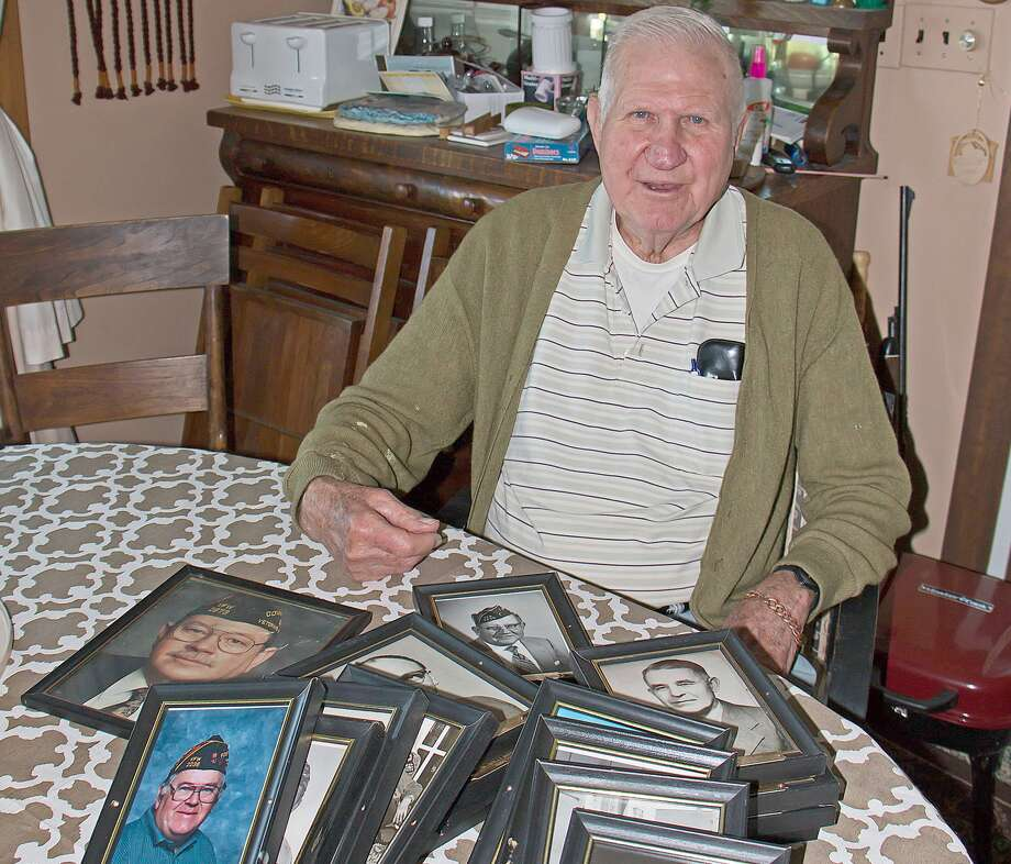 Joe Burzinski, a member of the Pigeon VFW, is on a mission to find relatives or friends of past post commanders that may be interested in having photos of their loved ones. Photo: Bill Diller/For The Tribune