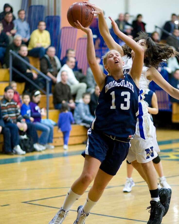 Immaculate's Colleen Preusse (13) gets her shot blocked from behind by Newtown's Riley Wurtz during their SWC game Friday night at Newtown High. Photo: Barry Horn / The News-Times Freelance
