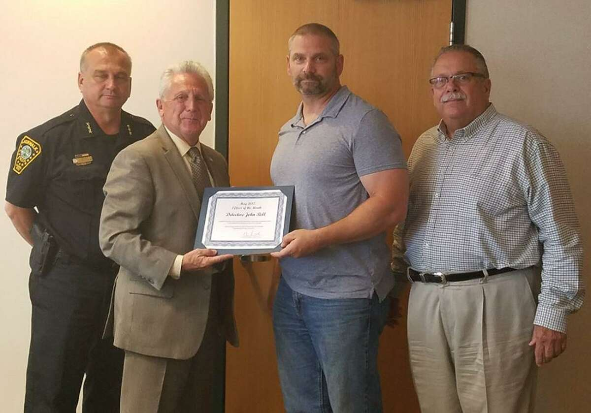 Detective John Bell, center, receives the May Officer of the Month award from Mayor Harry Rilling. Also pictured are Norwalk Police Chief Thomas Kulhawik (left) and police commissioner Charles Yost.