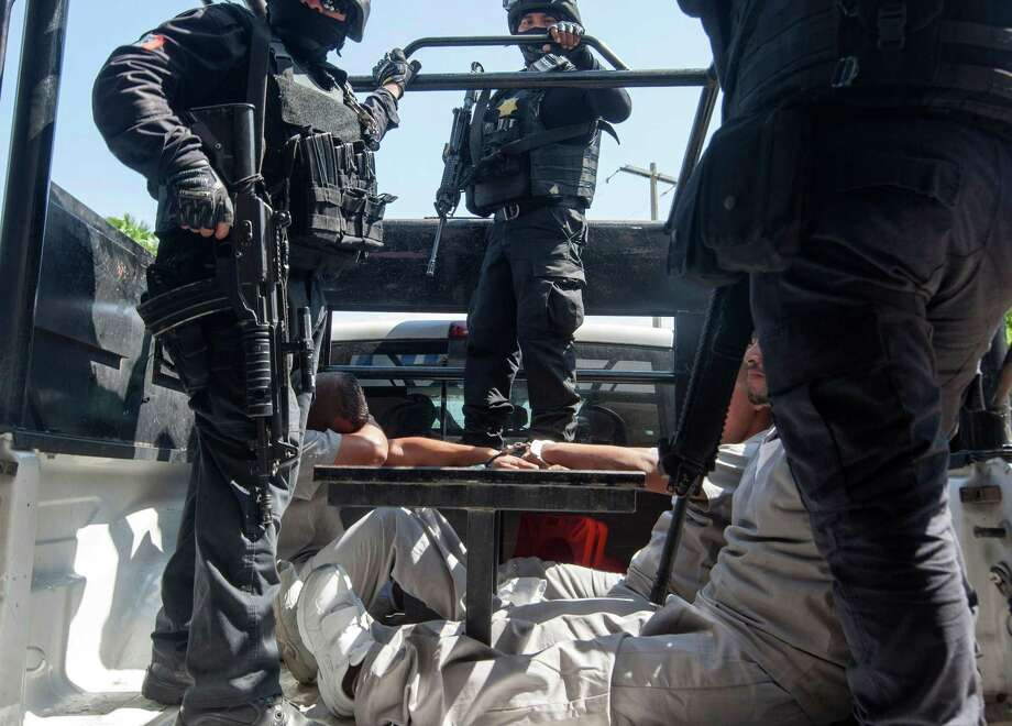 Inmates under guard in a truck in the prison in Reynosa, Tamaulipas state, Mexico during a visit by journalists on May 24, 2017. Two weeks ago, authorities found a tunnel and weapons buried inside the overcrowded prison in Reynosa, where 80 percent of the inmates belong to the Gulf Cartel.  / AFP PHOTO / Julio Cesar AGUILARJULIO CESAR AGUILAR/AFP/Getty Images Photo: JULIO CESAR AGUILAR, Stringer / AFP/Getty Images / AFP or licensors