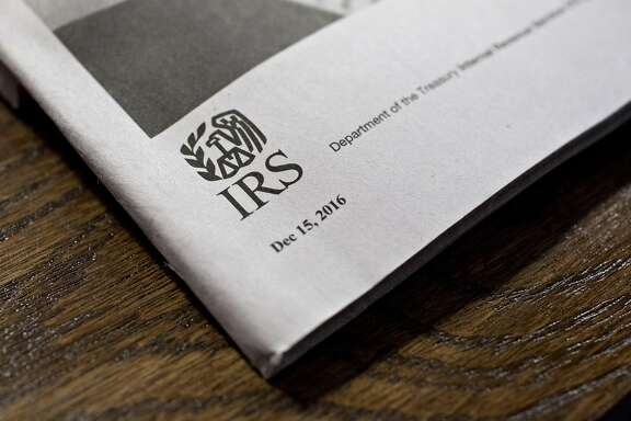 A U.S. Department of the Treasury Internal Revenue Service (IRS) logo is seen on an instruction book for a 1040 Individual Income Tax forms in Tiskilwa, Illinois, U.S., on Tuesday, March 28, 2017. Due to the Emancipation day holiday, this year's income taxes will need to be filed by April 18 instead of April 15. Photographer: Daniel Acker/Bloomberg