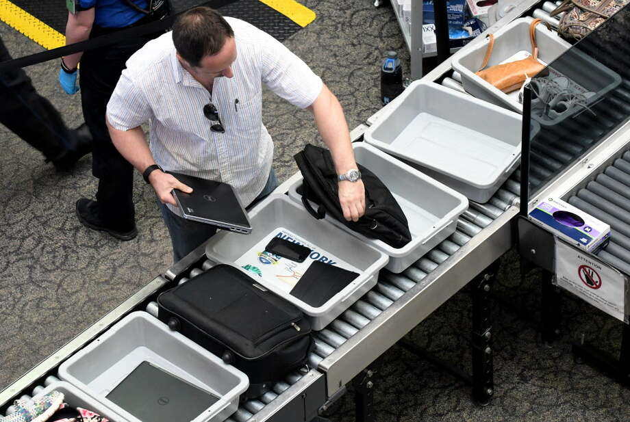 An air passenger removes his laptop computer from its bag for security screening at Albany International Airporton Tuesday, June 20, 2017, in Colonie, N.Y. (Will Waldron/Times Union) Photo: Will Waldron, Albany Times Union / 20040825A