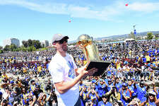 OAKLAND, CA - JUNE 15:  Klay Thompson #11 of the Golden State Warriors holds up the Larry O'Brien Trophy during the Victory Parade and Rally on June 15, 2017 in Oakland, California at The Henry J. Kaiser Convention. NOTE TO USER: User expressly acknowledges and agrees that, by downloading and or using this photograph, User is consenting to the terms and conditions of the Getty Images License Agreement. Mandatory Copyright Notice: Copyright 2017 NBAE (Photo by Noah Graham/NBAE via Getty Images)
