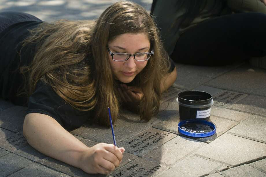 Destiny Sears, who will be a senior at Midland High in the fall, works to repaint the engraved names of local veterans at the Midland Veterans Memorial on Wednesday, June 21, 2017. Photo: Katy Kildee | Kkildee@mdn.net