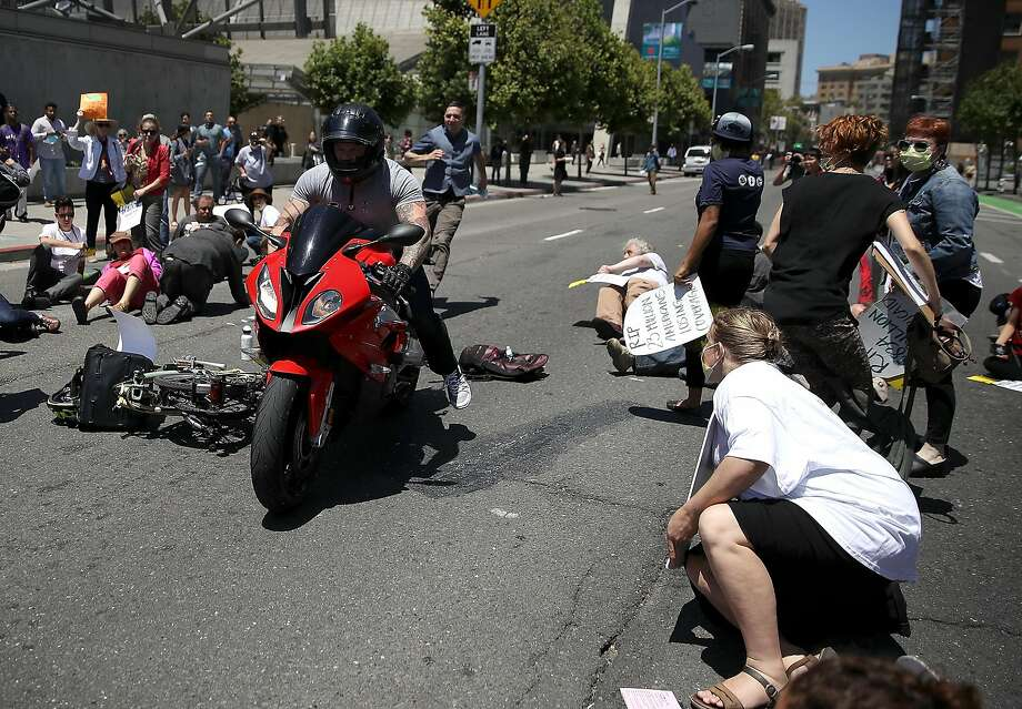 A motorcyclist rides through dozens of healthcare activists who were blocking a street while staging a die-in as the protested the Trumpcare bill on June 21, 2017 in San Francisco, California. The man narrowly missed the protesters on Seventh Street. Dozens of healthcare activists and senior citizens staged the protest outside the San Francisco Federal Building to express their opposition of the American Heathcare Act bill that is being drafted behind closed doors by Republican senators.  (Photo by Justin Sullivan/Getty Images) Photo: Justin Sullivan, Getty Images