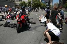 SAN FRANCISCO, CA - JUNE 21:  A motorcyclist rides through dozens of healthcare activists who were blocking a street while staging a die-in as the protested the Trumpcare bill on June 21, 2017 in San Francisco, California. The man narrowly missed the protesters on Seventh Street. Dozens of healthcare activists and senior citizens staged the protest outside the San Francisco Federal Building to express their opposition of the American Heathcare Act bill that is being drafted behind closed doors by Republican senators.  (Photo by Justin Sullivan/Getty Images)
