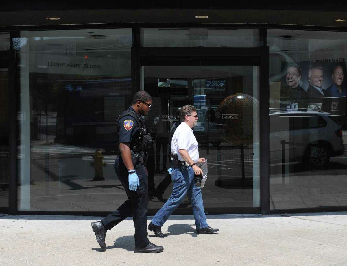 Accompanied by a police officer, Crime Scene Investigator Ed Rondano, right, carries an evidence bag of fecal matter from the scene where anti-Semitic graffiti was found on the windows of Rich Forum in Stamford, Conn. Monday, June 18, 2017. Swatikas and fecal matter were found on the windows Monday morning.