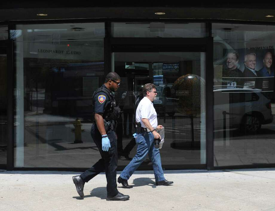 Accompanied by a police officer, Crime Scene Investigator Ed Rondano, right, carries an evidence bag of fecal matter from the scene where anti-Semitic graffiti was found on the windows of Rich Forum in Stamford, Conn. Monday, June 18, 2017. Swatikas and fecal matter were found on the windows Monday morning. Photo: Tyler Sizemore / Hearst Connecticut Media / Greenwich Time
