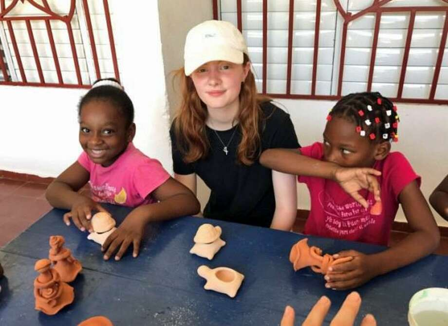 Seventh grader Niamh Nixon of Whitby School (center) sits with two girls from the Mariposa Foundation in the Dominican Republic on a recent service trip to the country. Photo: Contributed