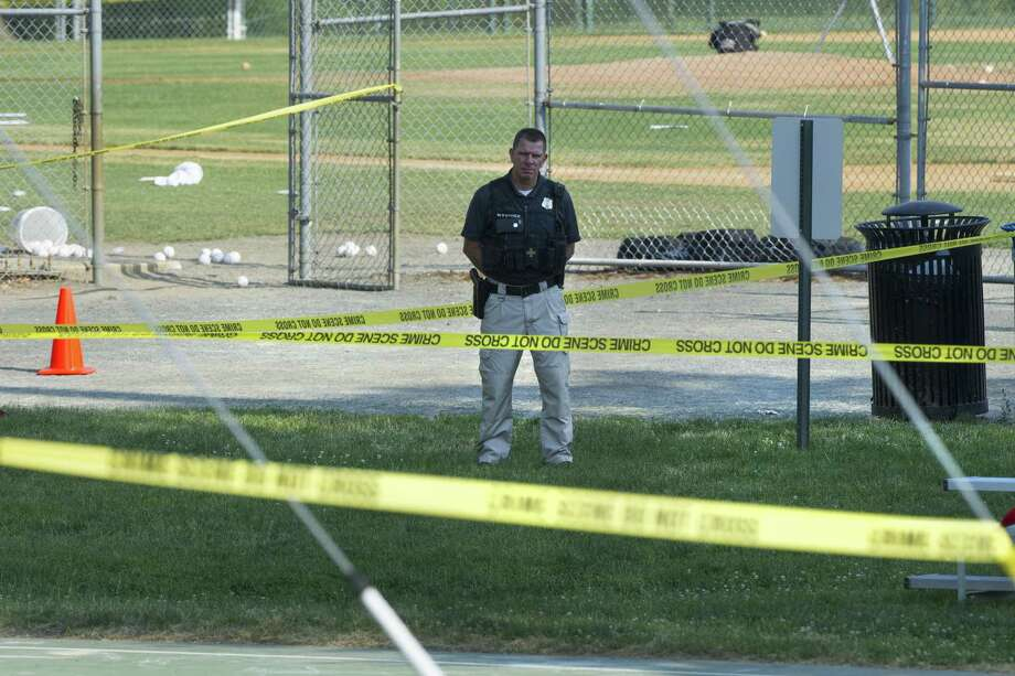 A police officer stands watch behind police tape near strewn baseballs on a field in Alexandria, Va., Wednesday after a multiple shooting involving House Majority Whip Steve Scalise of La. Photo: Cliff Owen / Associated Press / FR170079 AP