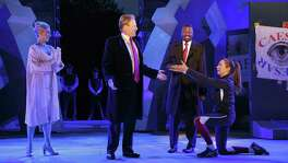 In this May 21, 2017, file photo provided by The Public Theater, Tina Benko, left, portrays Melania Trump in the role of Caesar's wife, Calpurnia, and Gregg Henry, center left, portrays President Donald Trump in the role of Julius Caesar during a dress rehearsal of The Public Theater's Free Shakespeare in the Park production of Julius Caesar in New York. The play has sparked controversy because of the Trump-like character.