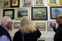 Visitors take in the Spring Paint-Out show at the Arnould Gallery in Marblehead, Mass., of plein air artists, including Brechin Morgan.