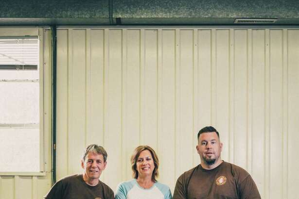 Sitting on a stack of local American black walnut lumber, Griffin Lee Artisans' wood of choice, are Daniel Lee, left, finish craftsman, sales and design consultant, Melissa Levethan, president and head of marketing, and Andrew Griffing, chief designer and master craftsman.