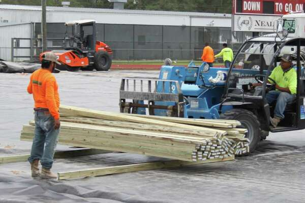 Construction workers move lumber over toward the visitor side of the Cleveland High School football field to continue their work on installing artificial turf on June 21.