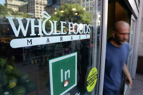 In this June 24, 2015, file photo, a shopper leaves a Whole Foods Market store in New York's Union Square. (AP Photo/Julie Jacobson, File)