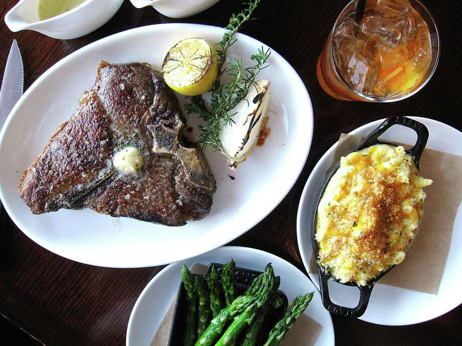 A T-bone steak, an old-fashioned cocktail, baked mac and cheese and asparagus at 18 Oaks, the steakhouse at the JW Marriott San Antonio Hill Country Resort & Spa Photo: Mike Sutter /Staff File Photo