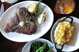 A T-bone steak, an old fashioned cocktail, baked mac and cheese and asparagus at 18 Oaks, the steakhouse at the JW Marriott San Antonio Hill Country Resort & Spa.