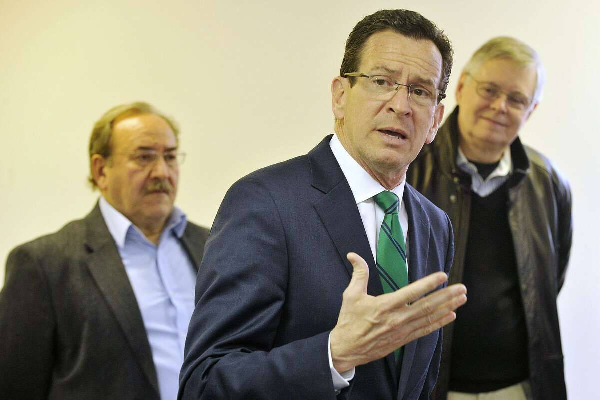 FILE - Gov. Dannel P. Malloy addresses a crowd of supporters as Democratic City Committee Chairman John Mallozzi, left, and Mayor David Martin look on during the governor's campaign kickoff party at the Democratic City Committee headquarters in Stamford, Conn., on Sunday, April 6, 2014.
