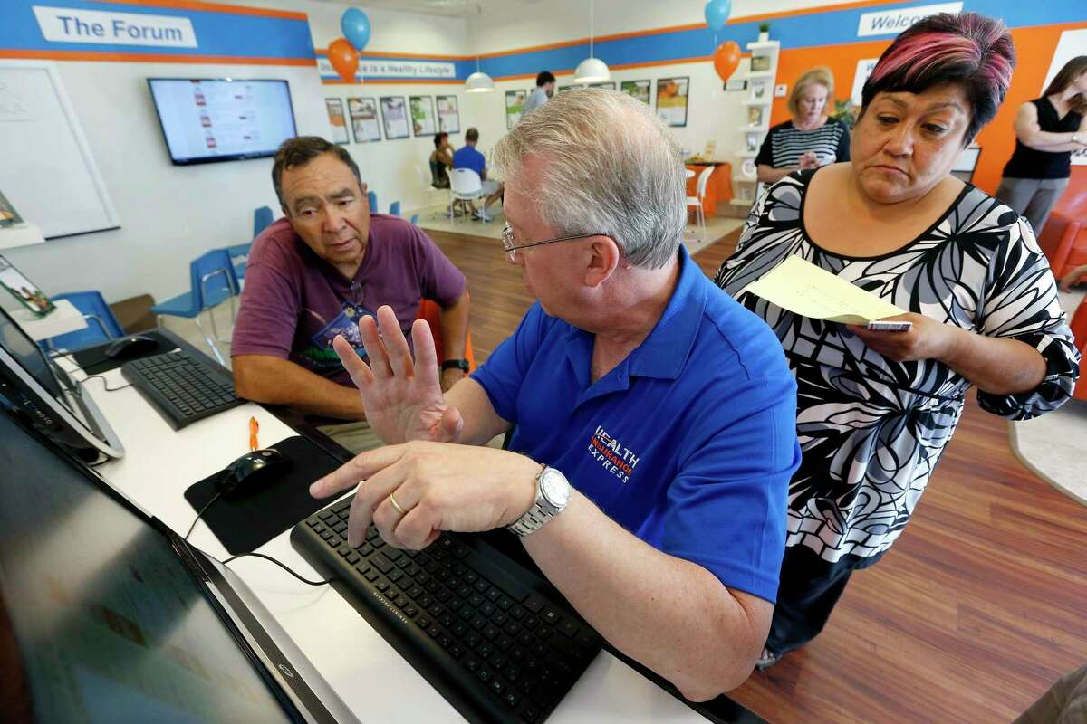FILE - In this Tuesday, Oct. 1, 2013, file photo, Alan Leafman, center, president of Health Insurance Express, Inc., helps Raquel Bernal, right, and her husband John Bernal, both of Apache Junction, Ariz., navigate the nation's health care insurance system online at the Health Insurance Express store in Mesa, Ariz. (AP Photo/Ross D. Franklin, File)