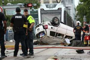 Metro Police and Houston firefighters investigate the scene of a fatal accident between three vehicles and a METRO train at the intersection of Main and McGowen streets Wednesday, June 21, 2017. .