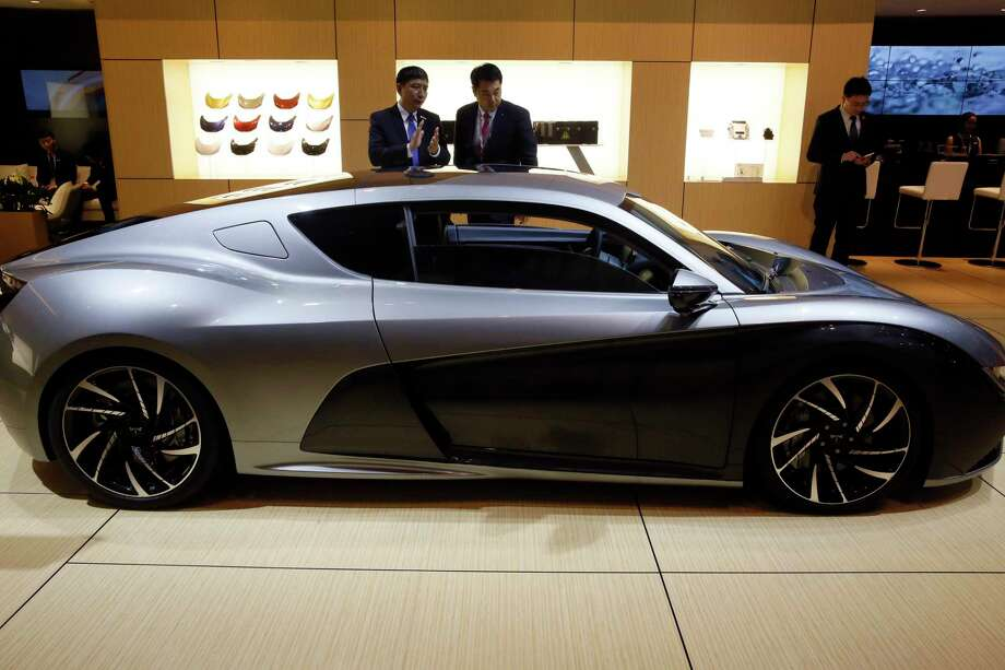 In this Wednesday, April 19, 2017 photo, visitors look at the Qiantu K50 displayed at the Shanghai auto show. Qiantu is part of a wave of fledgling automakers - all backed at least in part by Chinese investors - that are propelling the electric vehicle industry's latest trend: ultra-high-performance cars. (AP Photo/Ng Han Guan) Photo: Ng Han Guan, STF / Copyright 2017 The Associated Press. All rights reserved.