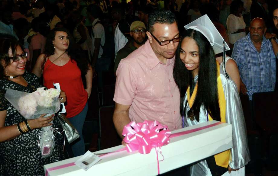 Graduate Gallerie Quezada is given a hug and a box of flowers by her dad Rafael at the conclusion of Bridge Academy's 20th Annual Commencement Exercises in Bridgeport, Conn., on Thursday June 21, 2017. Photo: Christian Abraham, Hearst Connecticut Media / Connecticut Post