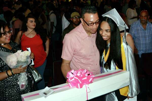 Graduate Gallerie Quezada is given a hug and a box of flowers by her dad Rafael at the conclusion of Bridge Academy's 20th Annual Commencement Exercises in Bridgeport, Conn., on Thursday June 21, 2017.