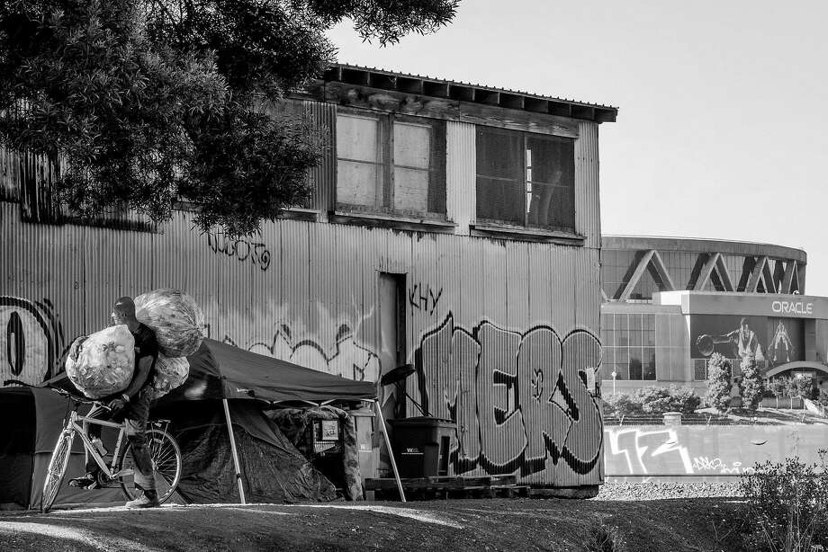 Tony Smith is loaded down with cans at his campsite outside Oracle Arena in Oakland as he prepares to bike to a nearby recycling center. Photo: Santiago Mejia, The Chronicle
