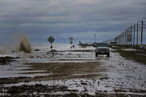 Cars navigate past waves and debris washing over State 87 as Tropical Storm Cindy approaches Wednesday in High Island.