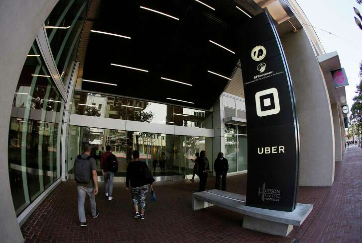 People make their way Wednesday into the building that houses the headquarters of Uber in San Francisco. Uber needs a new leader after former CEO and company founder Travis Kalanick resigned this week.