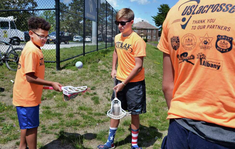 Albany and Casey Tarbay, 15, of Colonie toss around a lacrosse ball during the launch of the Lacrosse Communities Project ceremony at Albany High School Wednesday June 21, 2017 in Albany, NY. Albany will be the first of several cities across the country to implement the national lacrosse mentoring program which aims to provide opportunities for urban youth through the early introduction to Lacrosse. (John Carl D'Annibale / Times Union)