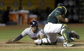 Houston Astros' Jake Marisnick, left, slides to score behind Oakland Athletics catcher Josh Phegley during the sixth inning of a baseball game Wednesday, June 21, 2017, in Oakland, Calif. (AP Photo/Ben Margot)
