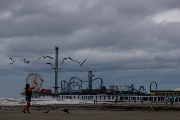 Natalie Hibbs feeds seagulls on the beach next to Pleasure Pier as Tropical Storm Cindy approaches the coast Wednesday, June 21, 2017 in Galveston.