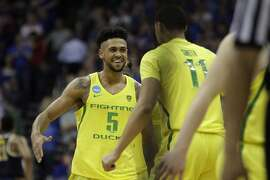 Oregon guard Tyler Dorsey (5) celebrates with Keith Smith (11) at the end of a regional semifinal against Michigan in the NCAA men's college basketball tournament, Thursday, March 23, 2017, in Kansas City, Mo. Oregon won 69-68. (AP Photo/Charlie Riedel)